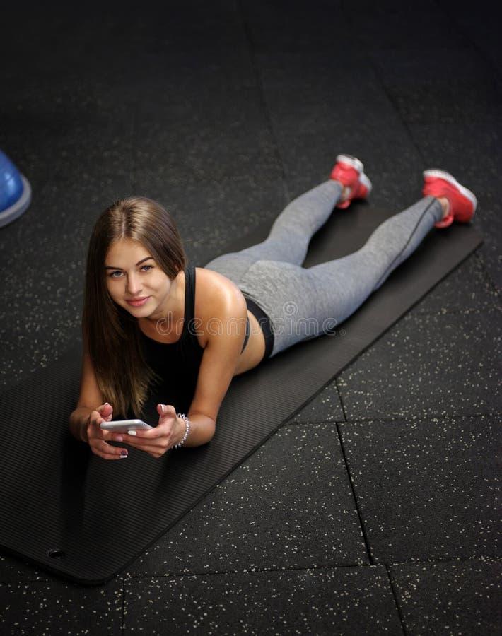 Los deportes que llevan bastante femeninos uniforman con un teléfono en un fondo del gimnasio Aptitud, actividad, y concepto del  fotografía de archivo libre de regalías