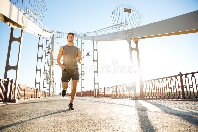 Los deportes sirven el funcionamiento a lo largo del puente moderno grande en la luz de la puesta del sol imagen de archivo libre de regalías