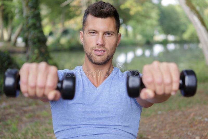 Los deportes sirven hacer entrenamiento con pesas de gimnasia al aire libre foto de archivo