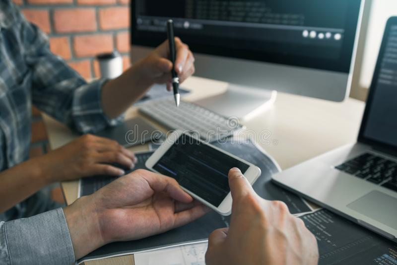 Los desarrolladores de software est?n utilizando los tel?fonos elegantes y est?n analizando juntos el c?digo escrito en el progra imagen de archivo libre de regalías