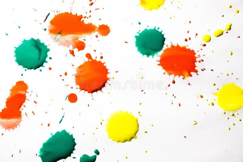Los descensos de la pintura roja, amarilla y verde se rocían en un fondo blanco fotos de archivo