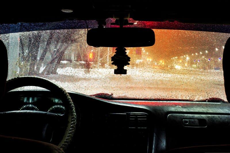los descensos hermosos del agua en el parabrisas del coche con los limpiadores de cristal se giraron, durante una tempestad de tr foto de archivo