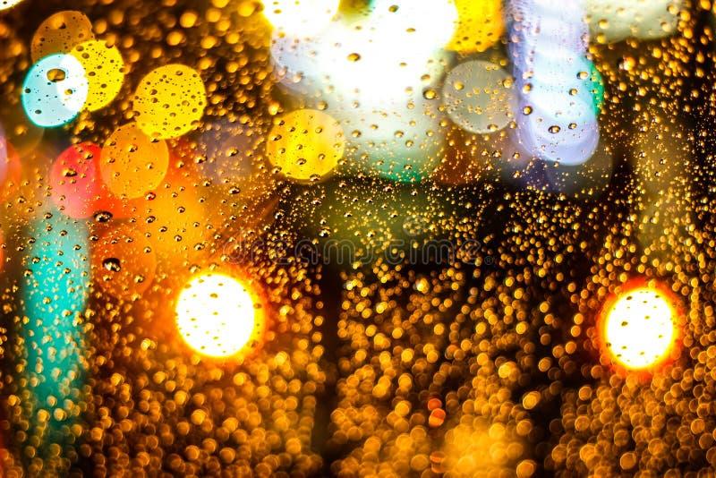 Los descensos sobre el vidrio, lluvia, noche se encienden, imagen de archivo libre de regalías