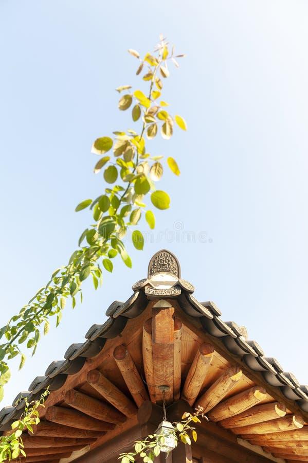 Los detalles arquitectónicos de aleros de madera y del tejado de la baldosa cerámica terminan de casa de la tradición en el puebl fotos de archivo