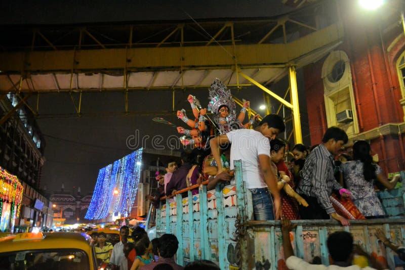 Los devotos transportan un ídolo en Durga Puja a fotografía de archivo