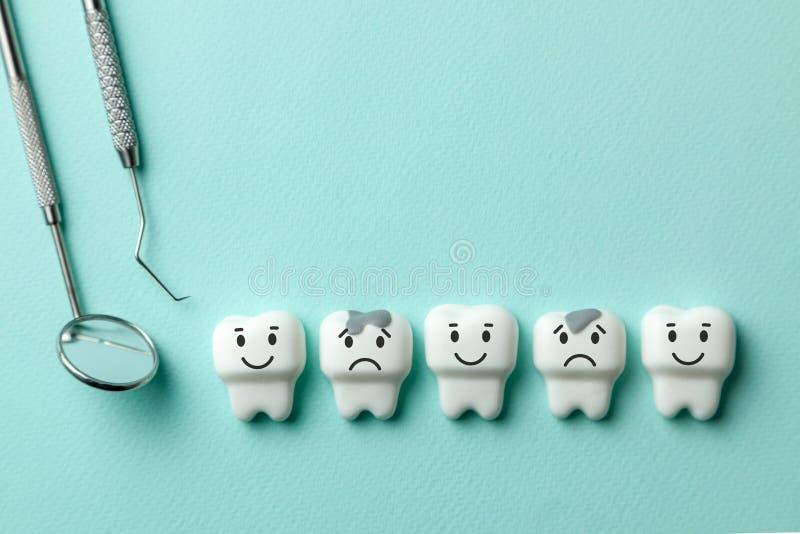 Los dientes blancos sanos están sonriendo y el diente con la carie está triste en las herramientas verdes espejo, gancho del fond imagen de archivo libre de regalías