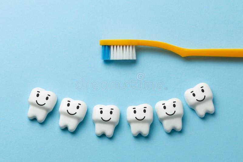 Los dientes blancos sanos est?n sonriendo en fondo azul con el cepillo de dientes imagenes de archivo