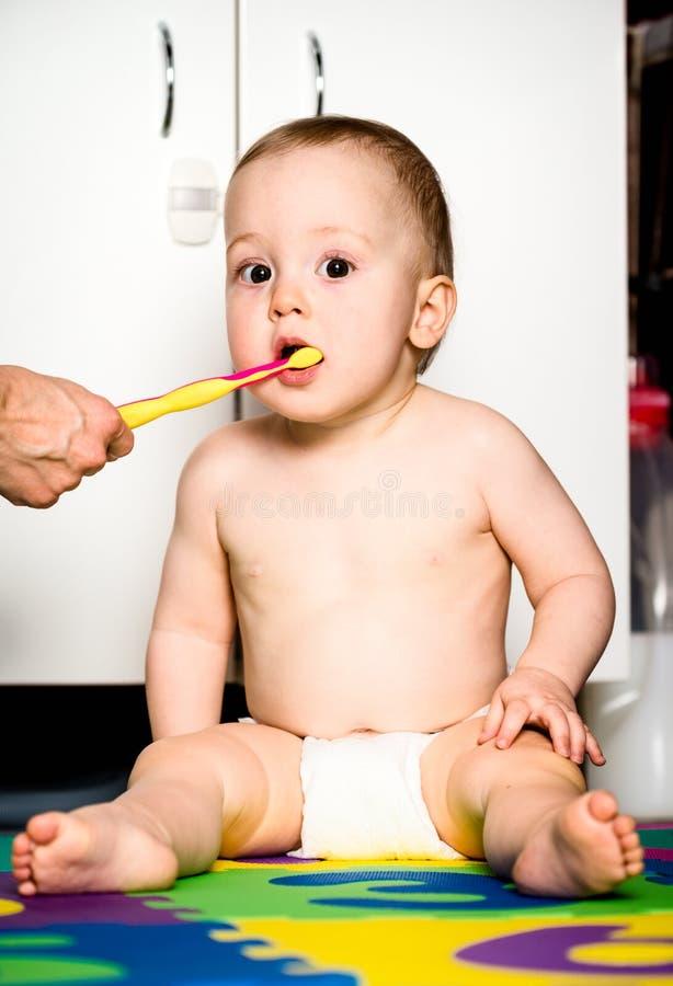 Los dientes de bebé de la limpieza de la madre foto de archivo libre de regalías