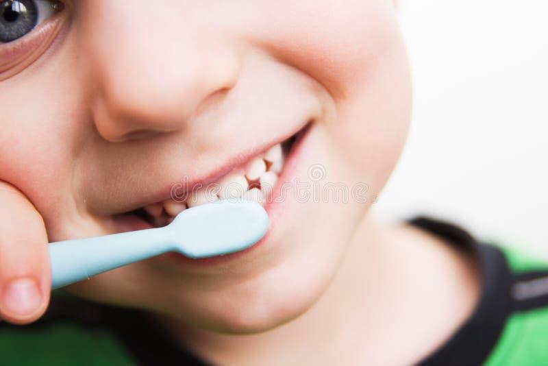 Los dientes del niño con un cepillo de dientes imagenes de archivo