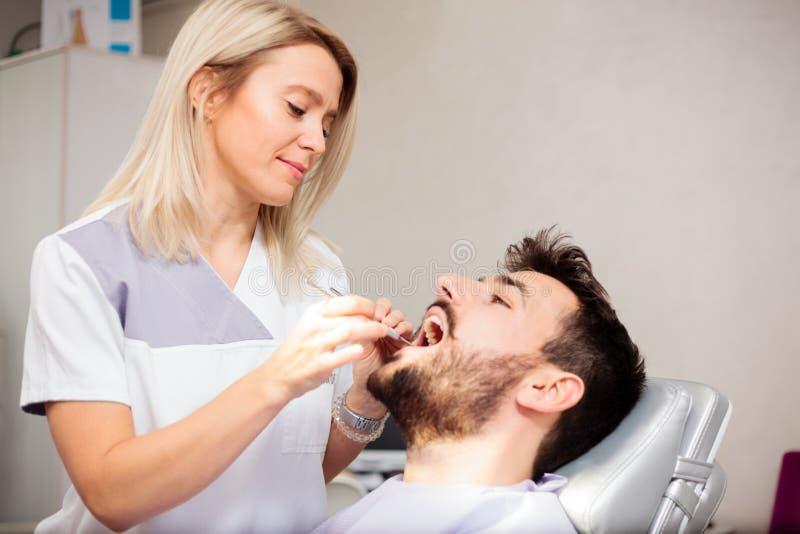 Los dientes del paciente masculino de examen del dentista de sexo femenino joven en una clínica dental imagen de archivo