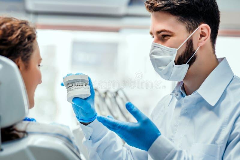 Los dientes dentales de la arcilla del dentista del molde platean la caries modelo del molde que muestra de cer?mica del paciente fotos de archivo