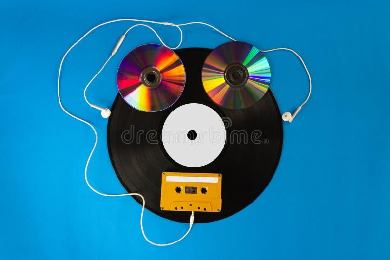 Los discos de vinilo y el CD viejos con la cinta de casete audio crean forma un robot y los auriculares del oído en fondo azul fotografía de archivo