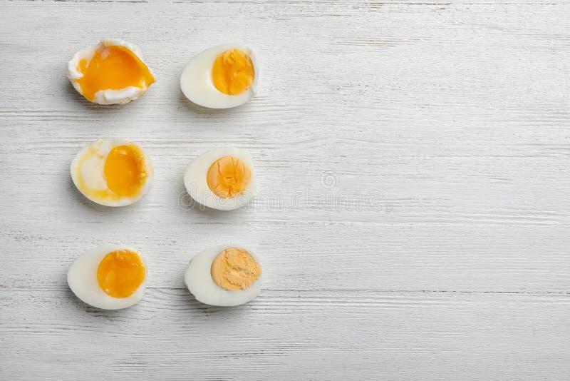 Los diversos tipos de huevos hervidos en el fondo de madera blanco, plano ponen con el espacio para el texto imágenes de archivo libres de regalías