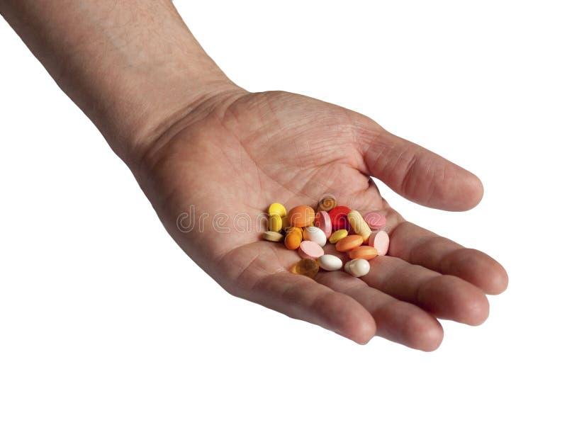 Los doctores dan sostener muchas p?ldoras coloridas aisladas en el fondo blanco Drogas, apego de la medicaci?n Tenencia il?cita y imagenes de archivo