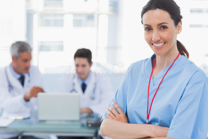 Los doctores que usaban el ordenador portátil y a una enfermera sonriente cruzaron sus brazos fotografía de archivo