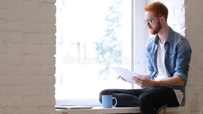 Los documentos de la lectura, papeleo, relajan al hombre que se sienta en la ventana, barba imagen de archivo libre de regalías
