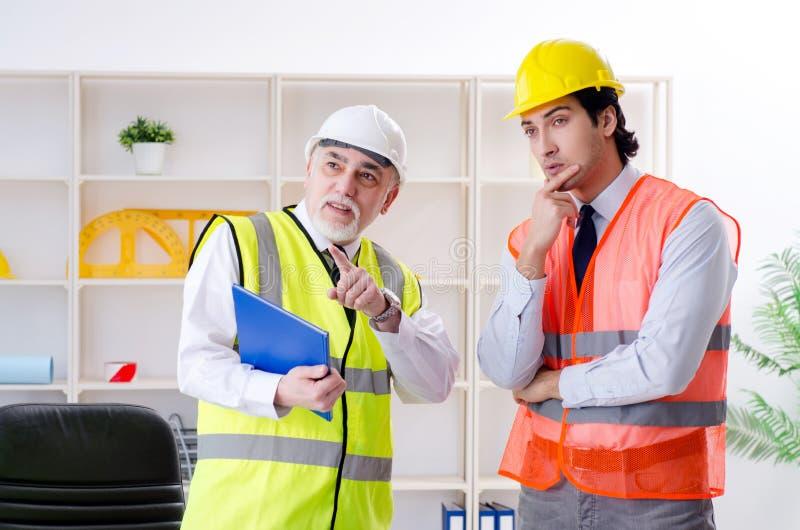 Los dos colegas de los ingenieros que trabajan bajo proyecto imagenes de archivo