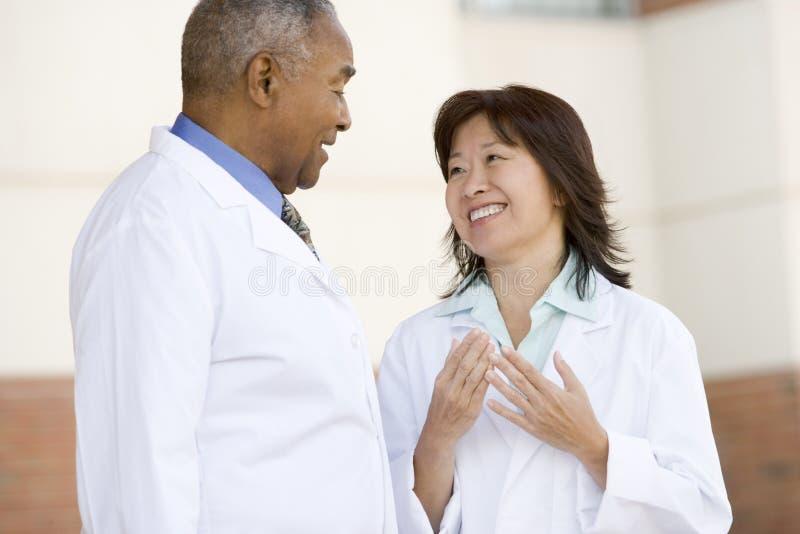 Los dos doctores Standing Outside A Hospital imagenes de archivo