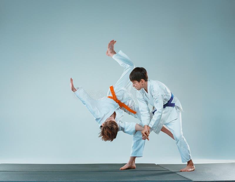Los dos muchachos que luchan en el entrenamiento del Aikido en escuela de artes marciales Forma de vida y concepto sanos de los d fotografía de archivo libre de regalías