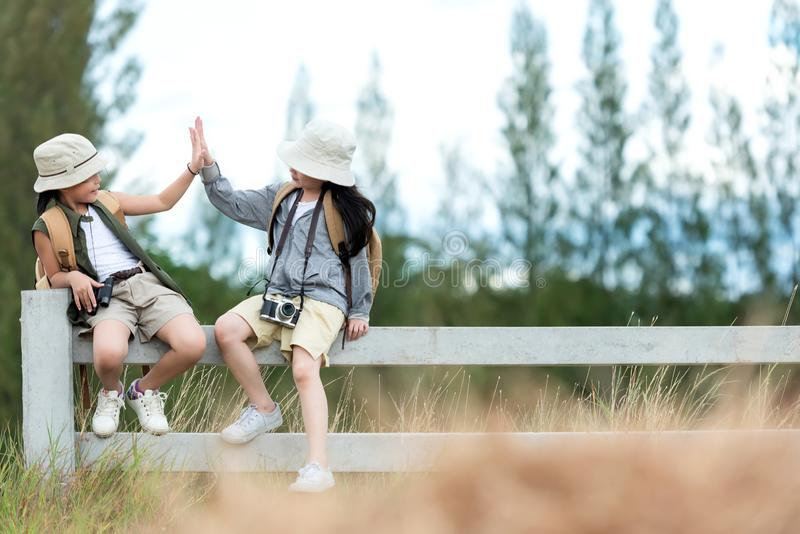 Los dos niños asiáticos aumentar me dan cinco y sentarse en el aire libre, la aventura y el turismo blancos de la cerca para el d imagen de archivo