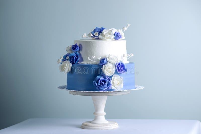 Los dos pasteles de bodas blancos y azules con gradas hermoso adornados con las flores azucaran rosas Concepto de postres elegant imagen de archivo libre de regalías