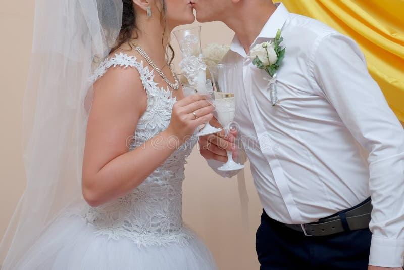 Los dos recienes casados guardan el champán y besarse imagenes de archivo