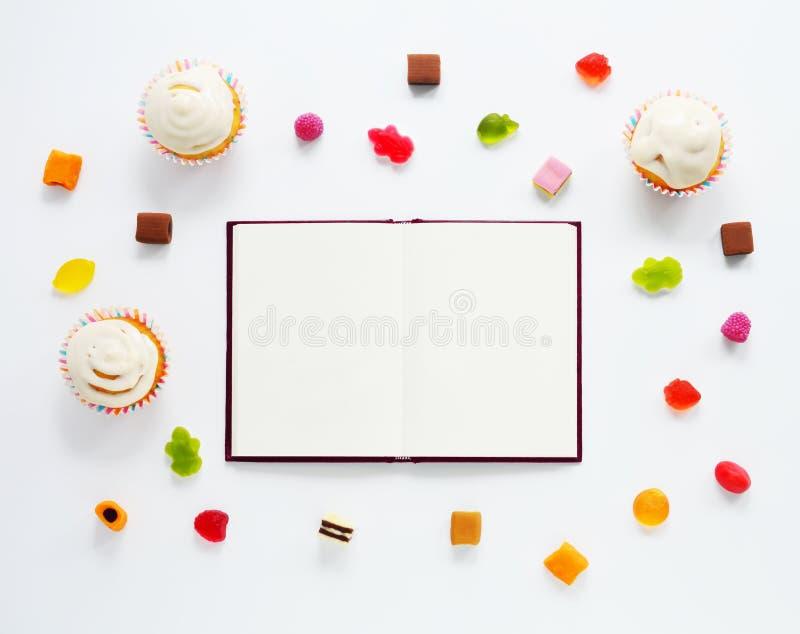 Los dulces imitan para arriba con el cuaderno foto de archivo