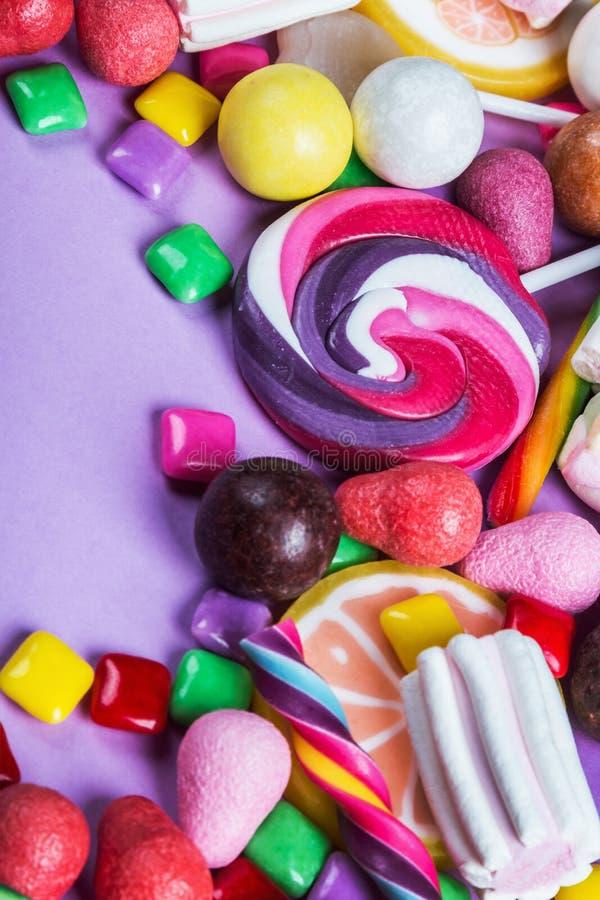Los dulces son diferentes en el fondo púrpura, piruletas, goma, candi imagen de archivo libre de regalías