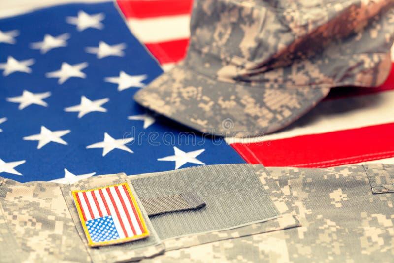Los E.E.U.U. señalan con el uniforme militar de los E.E.U.U. sobre él - el tiro del estudio por medio de una bandera Imagen filtr imagenes de archivo