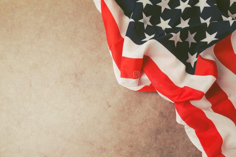 Los E.E.U.U. señalan por medio de una bandera sobre el papel del vintage con el espacio de la copia 4to del fondo de julio imagen de archivo