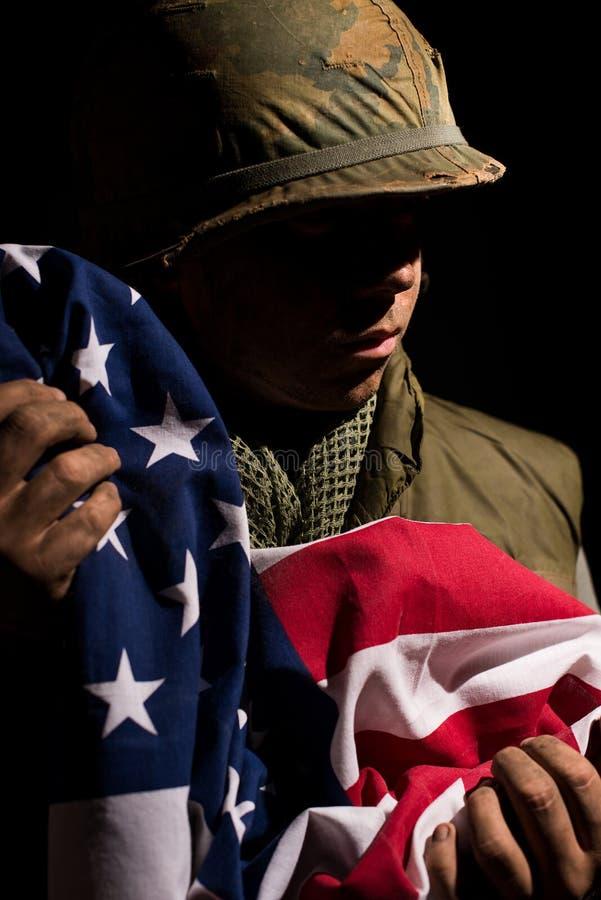 Los E.E.U.U. Marine Vietnam War que sostiene la bandera americana foto de archivo