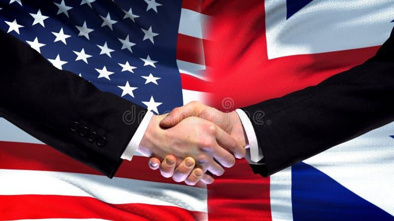 Los E.E.U.U. y apretón de manos de Gran Bretaña, fondo internacional de la bandera de la amistad fotos de archivo