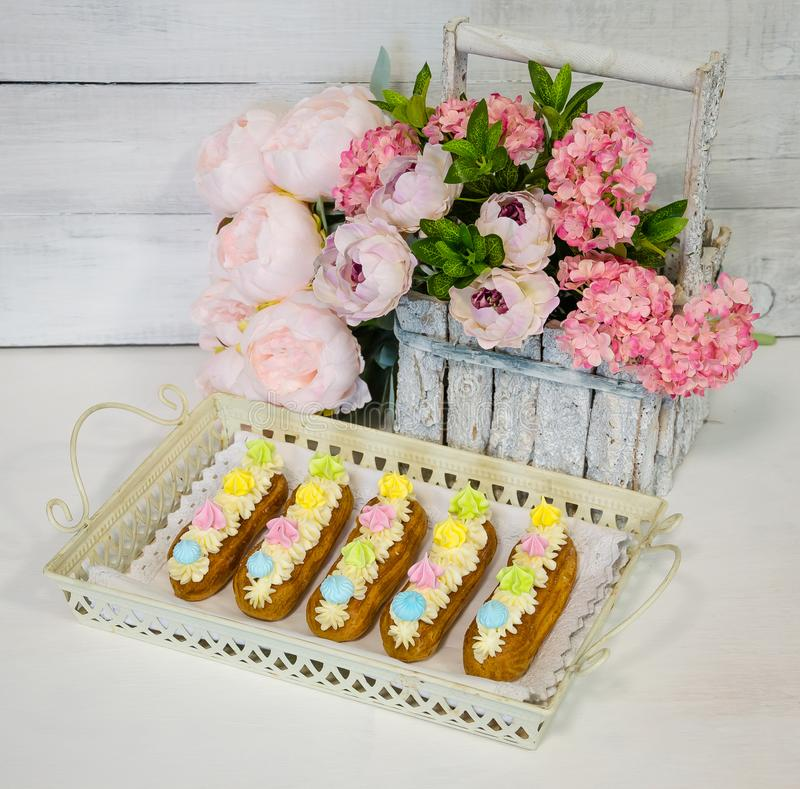 Los eclairs con el queso cremoso de la vainilla adornado con los merengues foto de archivo