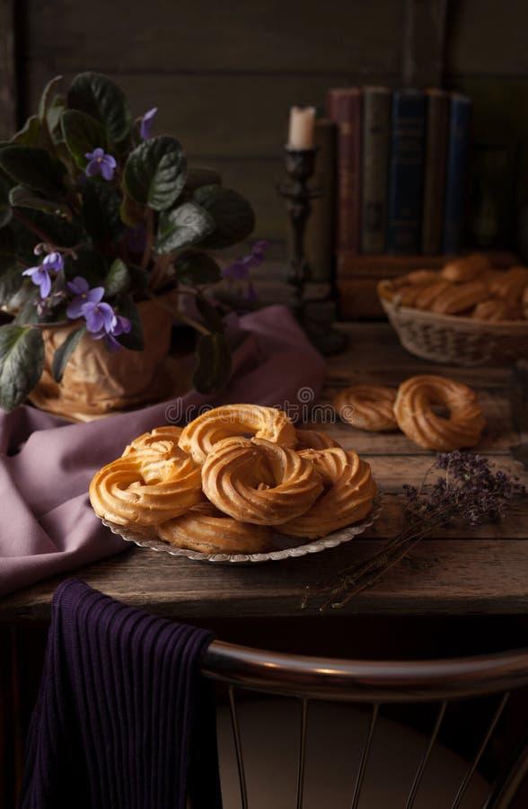 Los Eclairs o el postre delicioso de los pasteles del profiterole llenaron de crema azotada imagen de archivo