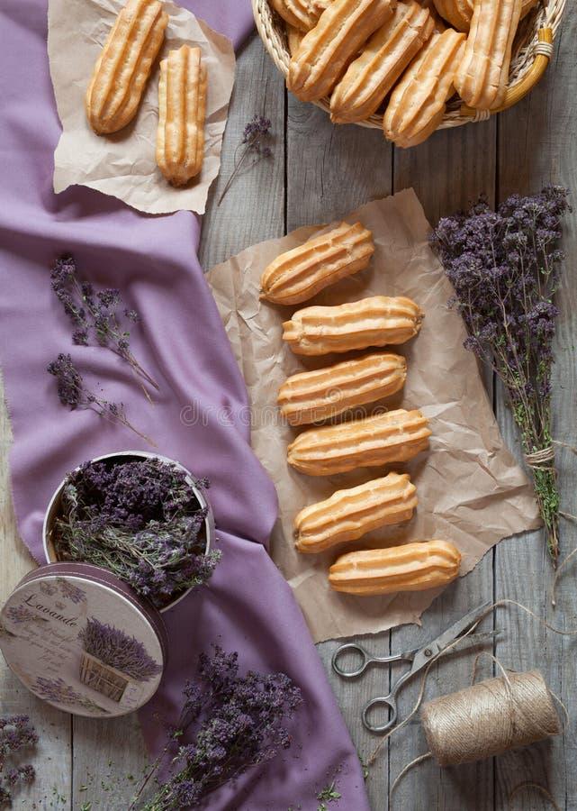 Los eclairs o el postre tradicionales de los pasteles del profiterole llenaron de crema azotada fotos de archivo