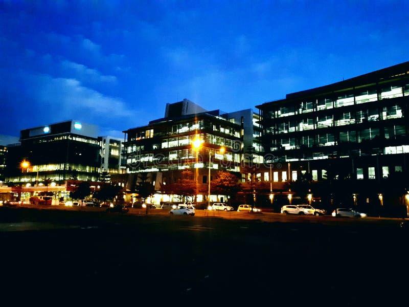 Los edificios bajo igualación del cielo azul con la ciudad se encienden fotografía de archivo