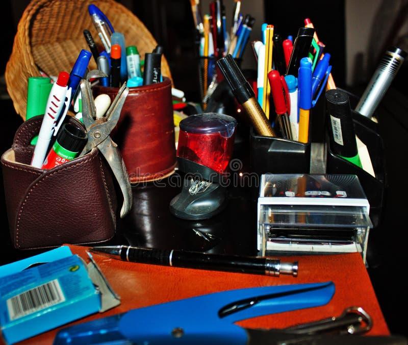 los efectos de escritorio varían las plumas, lápices, borradores, sellos llenaron todo para arriba fotos de archivo