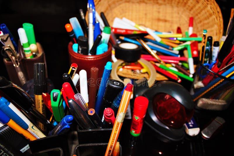 los efectos de escritorio varían las plumas, lápices, borradores, sellos llenaron todo para arriba imagenes de archivo