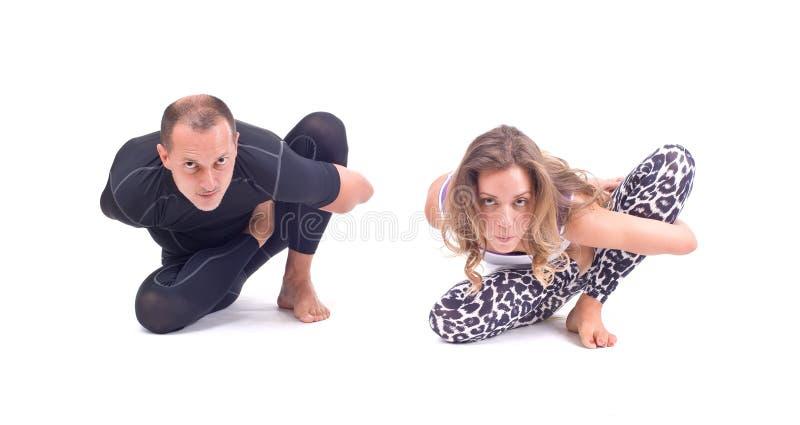Los ejercicios practicantes de la yoga en el grupo/Ray de luz presentan - Marichyasana imagen de archivo libre de regalías