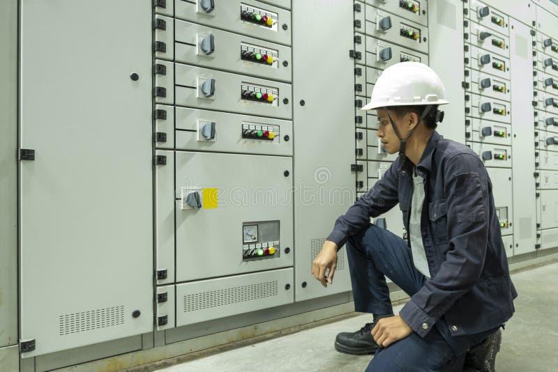 Los electricistas est?n comprobando paneles de control el?ctricos en plantas industriales imagen de archivo libre de regalías