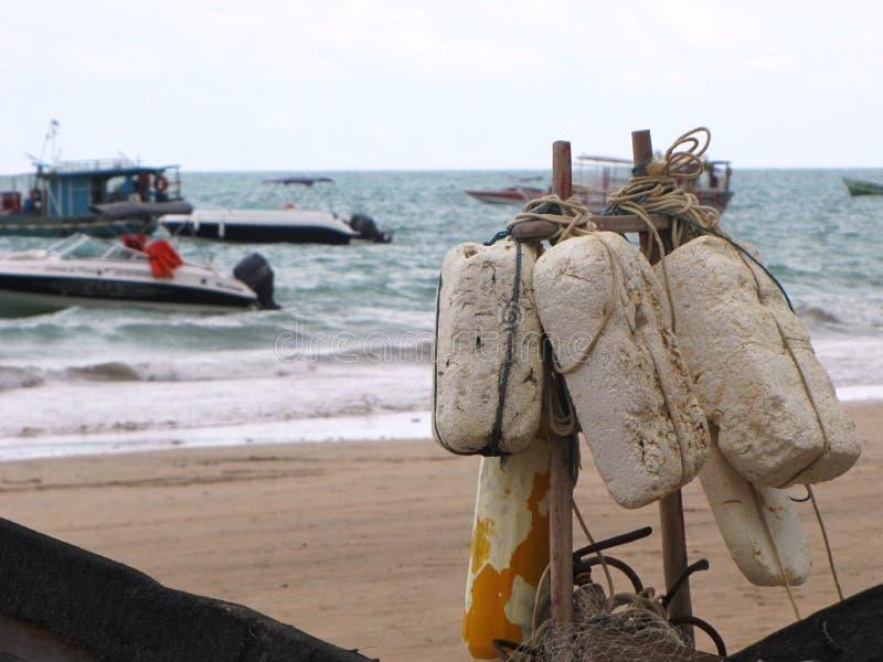 Los elementos de la pesca se encaramaron en la playa con el mar en el fondo imagen de archivo
