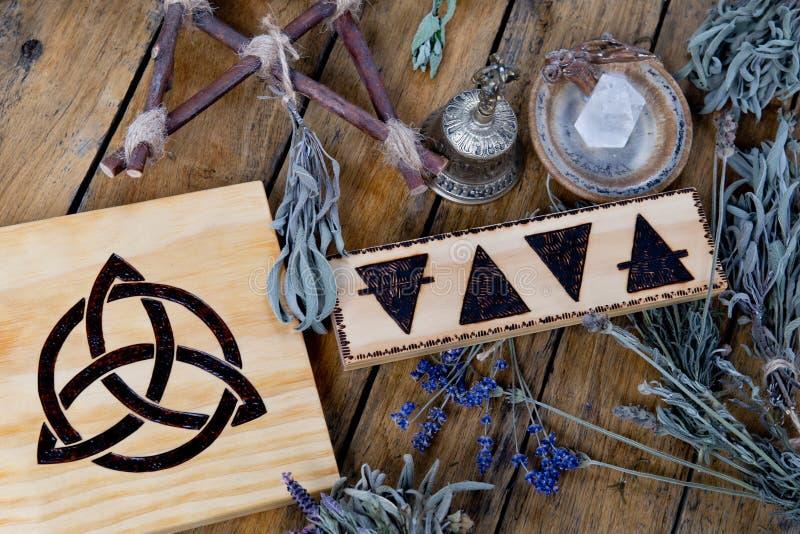 Los elementos - símbolos de la tierra, del fuego, del agua, del aire y de Triquetra - con la campana, el cristal de cuarzo, el pe imagen de archivo