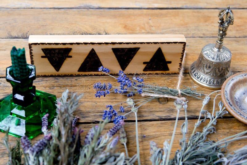 Los elementos - tierra, fuego, agua, aire con la campana de cobre amarillo, vela verde y paquetes de hierbas secadas en fondo de  imágenes de archivo libres de regalías
