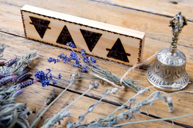 Los elementos - tierra, fuego, agua, aire con la campana de cobre amarillo y paquetes de hierbas secadas en fondo de madera fotografía de archivo