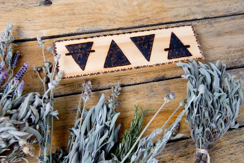 Los elementos - tierra, fuego, agua, aire con los paquetes de hierbas secadas en fondo de madera imagen de archivo