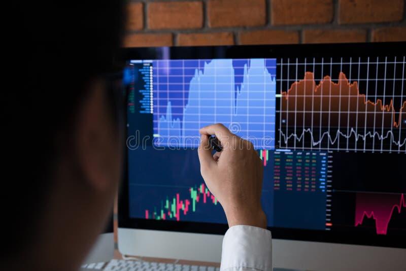 Los empleados analizan el gráfico del mercado de acción usando una pluma que señalan a la pantalla de ordenador imagen de archivo