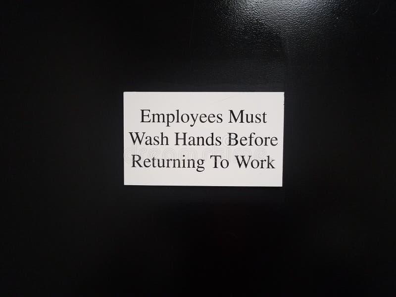 Los empleados blancos deben lavar las manos antes de volver a la muestra del trabajo en puerta negra imagenes de archivo