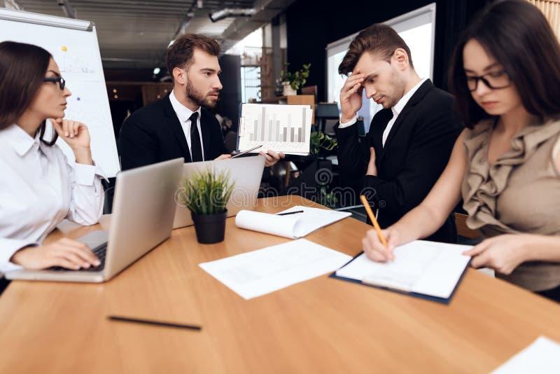 Los empleados de la compañía celebran una reunión en la tabla fotografía de archivo