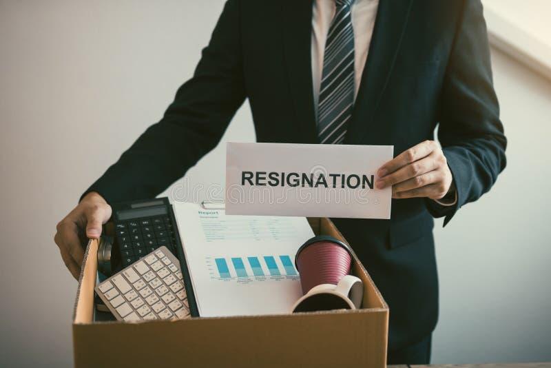 Los empleados de sexo masculino están guardando sus propios artículos en el escritorio porque están a punto de ir a dimitir con e imagen de archivo