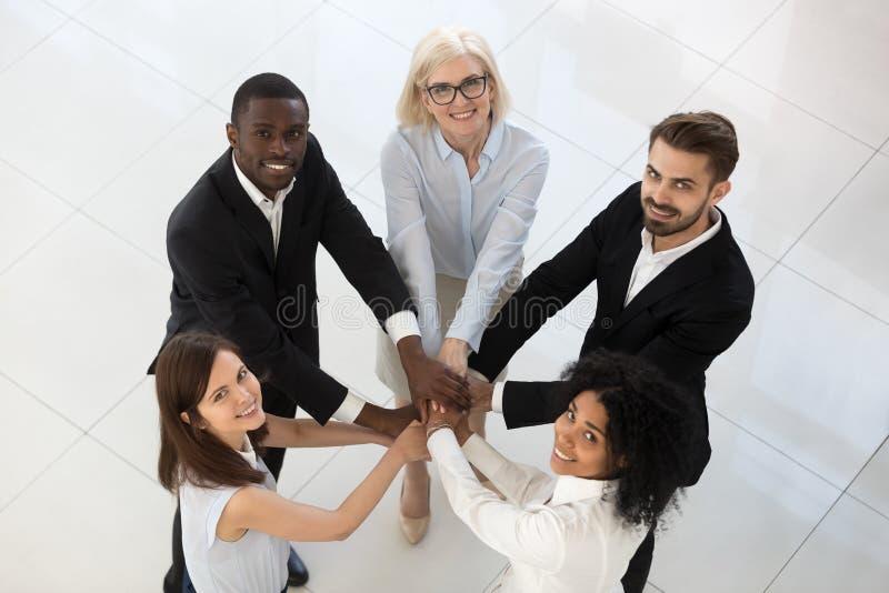 Los empleados diversos sonrientes del equipo apilan la pila de opinión superior de las manos imágenes de archivo libres de regalías